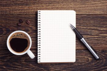 Cup of coffee, pen and notepad on wooden background. Top view
